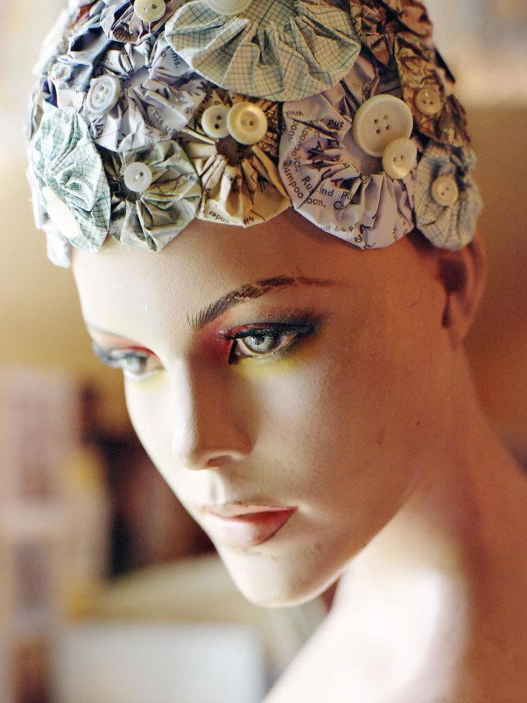A mannequin with a bath hat on its head made from intricately folded paper and buttons.