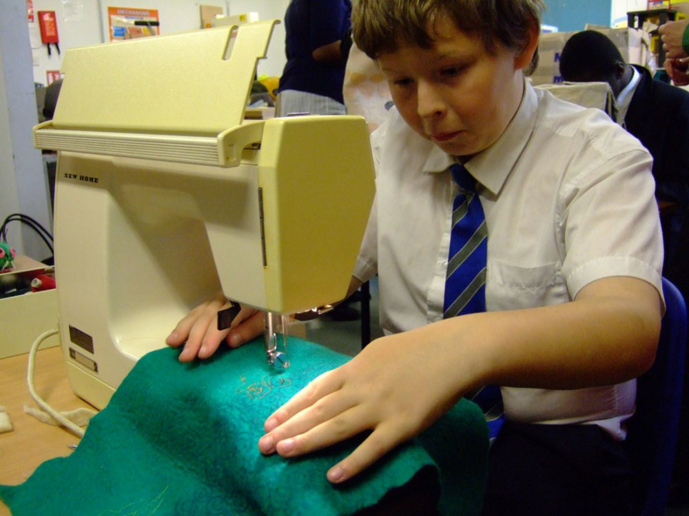 A young boy tentatively uses a sewing machine to sew an intricate design into a teal blue fabric.