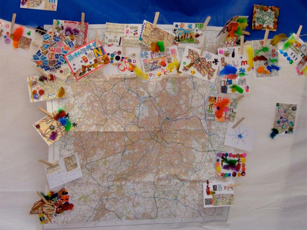 A large map of Birmingham placed on the wall is surrounded by small collages made by the public.