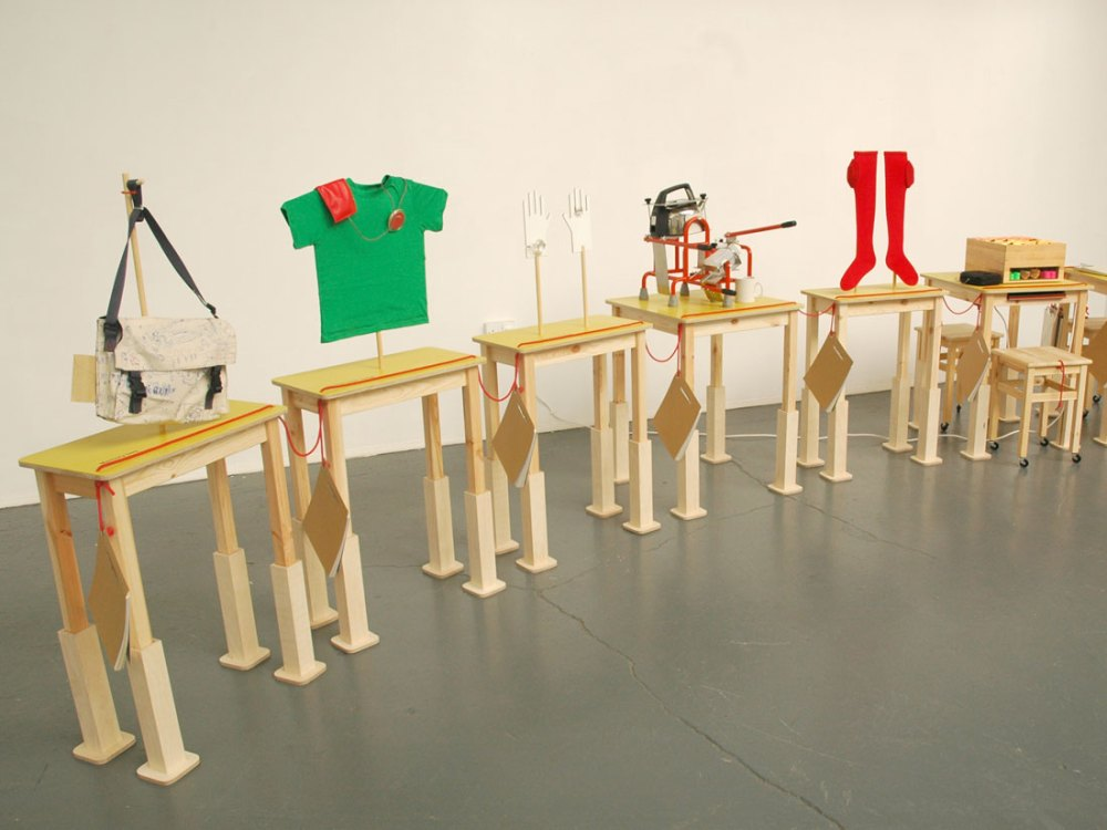 An exhibition with six small wooden tables with various objects placed on top of them including a bag.