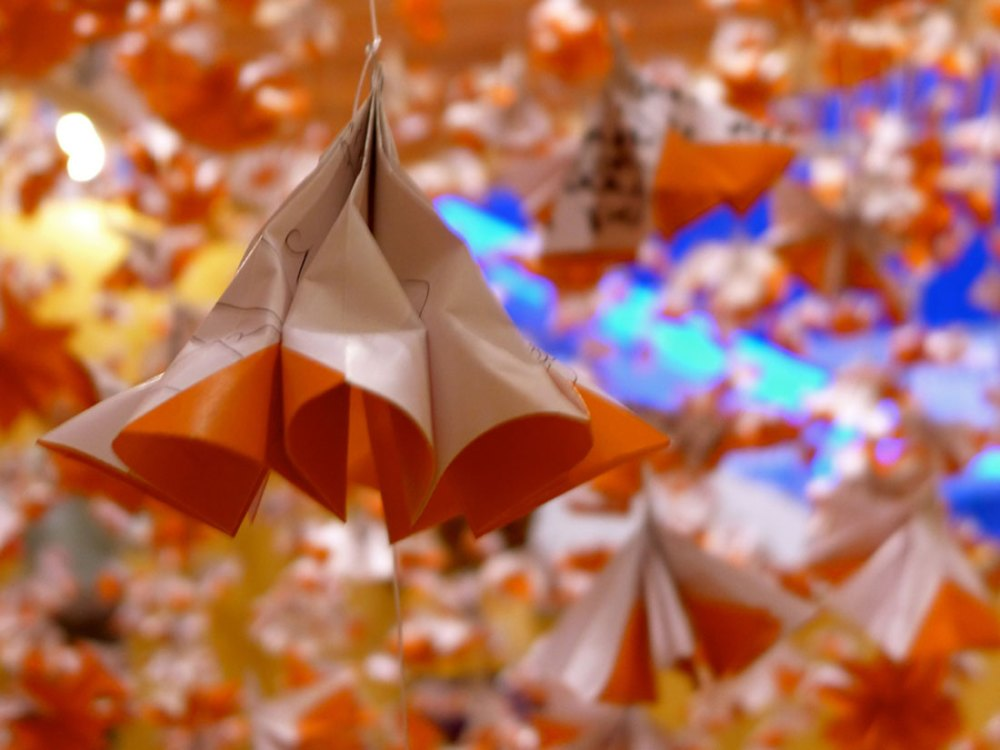 A geometric shape made from origami paper hangs from the ceiling using string, with more in the background.