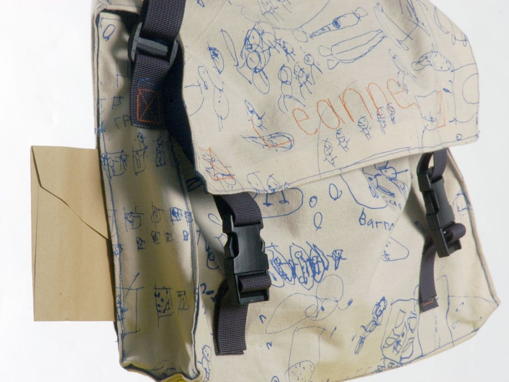 A close up of a white bag with various drawings and writing from children printed on to it.