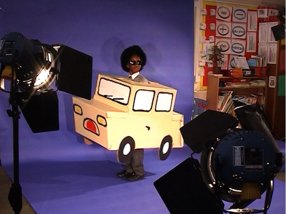 A young boy in sunglasses and a cardboard car stands infront of a blue screen with various lights on him.