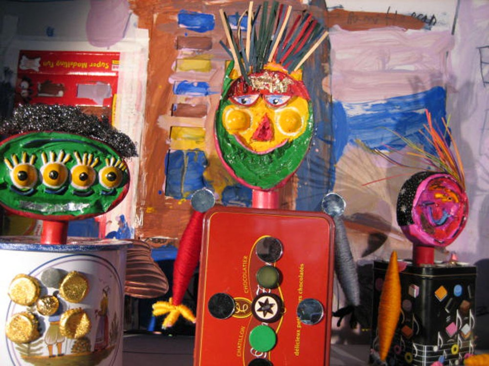 Three brightly painted figures made from found objects including tin boxes.