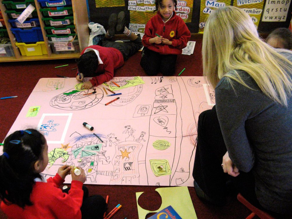Three children draw on to a large piece of paper using pens whilst a lady supervises.