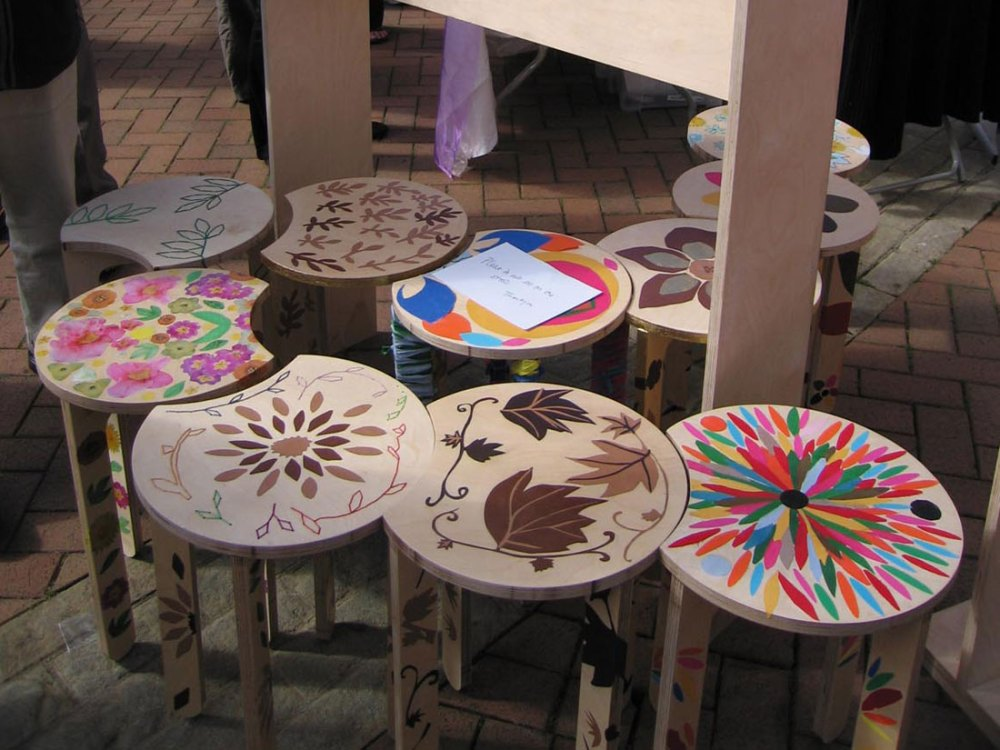 Ten stools sit next to one another with various nature themed designs stuck and stitched on to them.
