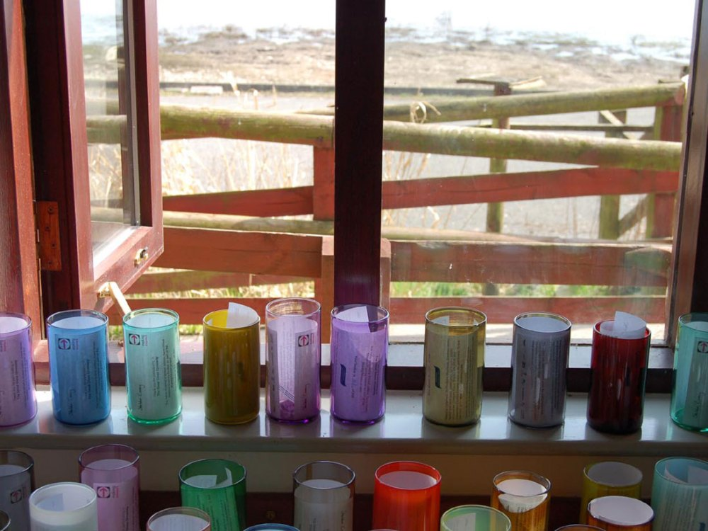 Tall glass beakers of various colours and opacities sit on a window sill with paper inside of them.