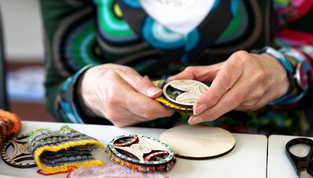 A pair of hands intricately embroider around and inside a wooden disc.