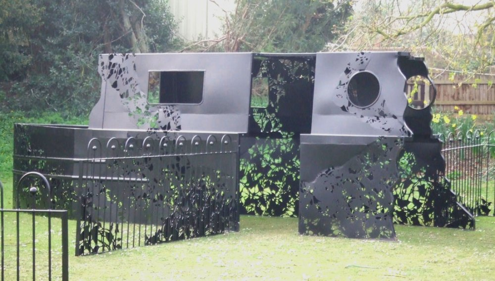 Artists commission of a part constructed boat and gates made of sheet black metal with leaves lasercut from the material.