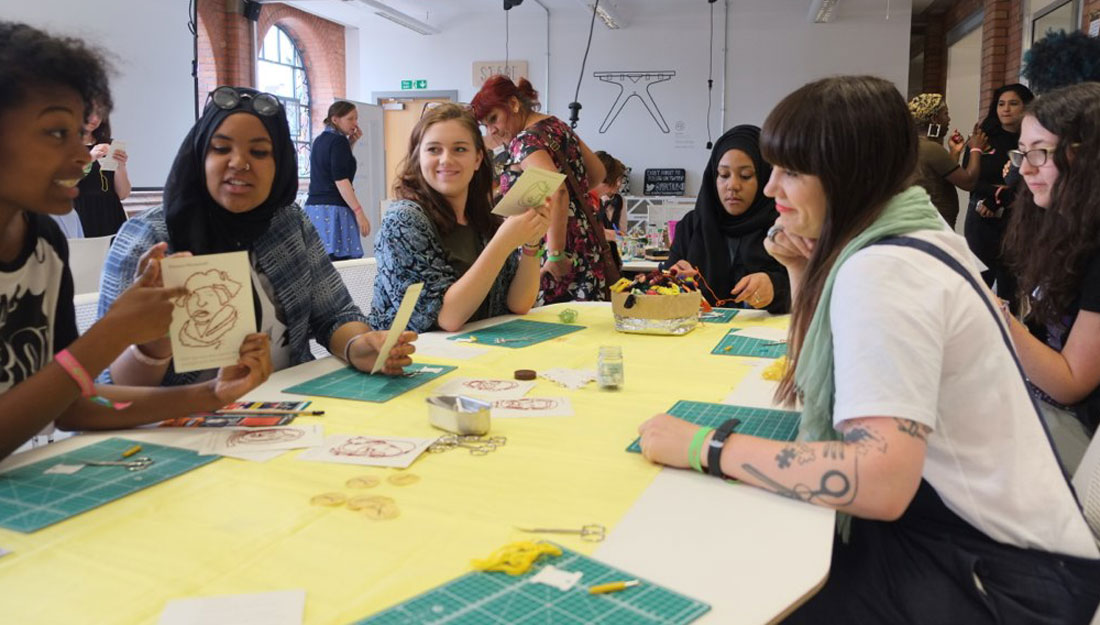 A group of people sit around a table discussing the stitched cards they have produced.