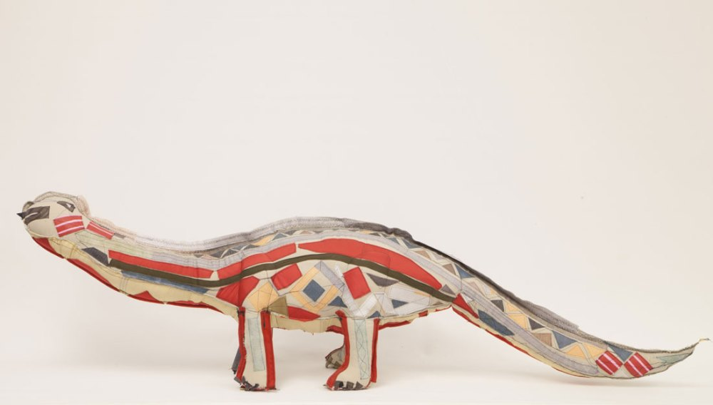 A patchwork 3D dinosaur made of various textiles.