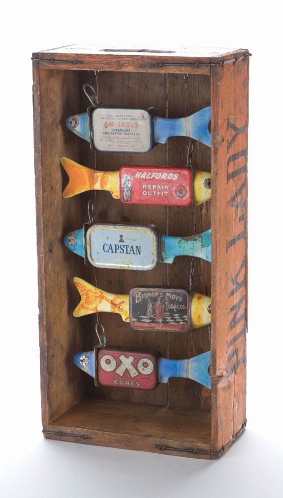 Five fish made from found metal hang inside a wooden crate.