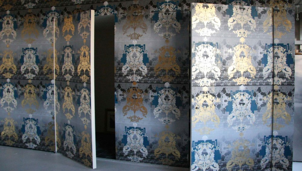 A intricate, traditional print in golds, silvers, blacks and greys sit on various boards.
