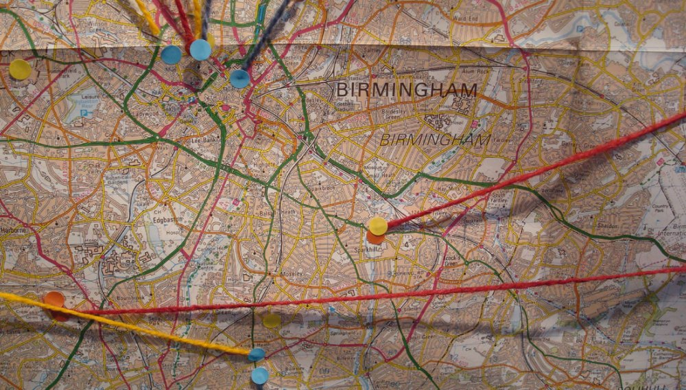 A map of Birmingham with various pins and stickers at locations.