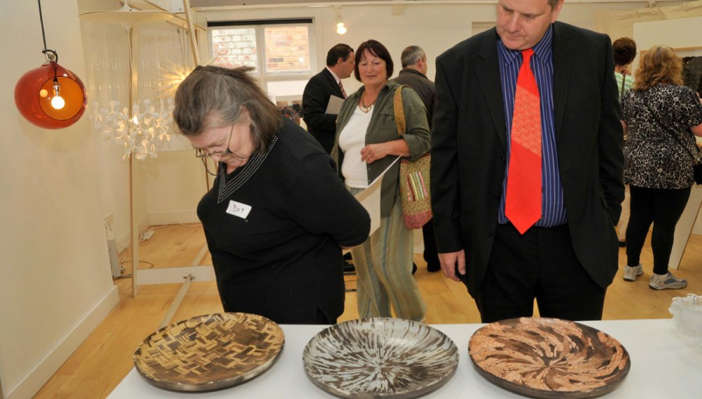A man and woman admire three ceramic dishes on a table at an exhibition.