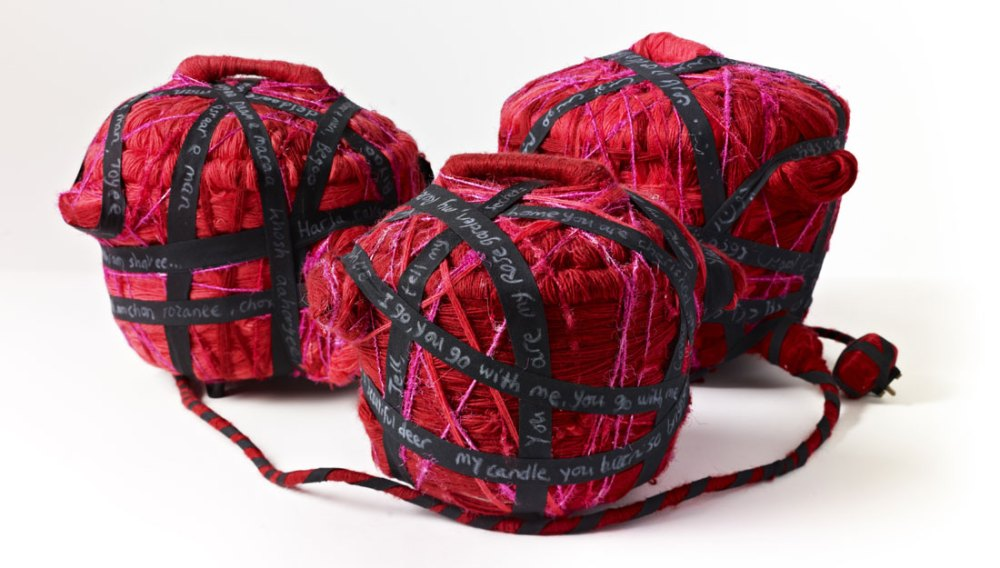 Three pots covered in yarn and thread sit next to each other.