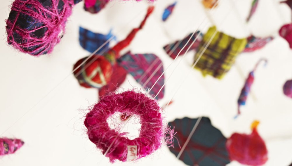 Various pieces of textile and yarn float from the ceiling on string