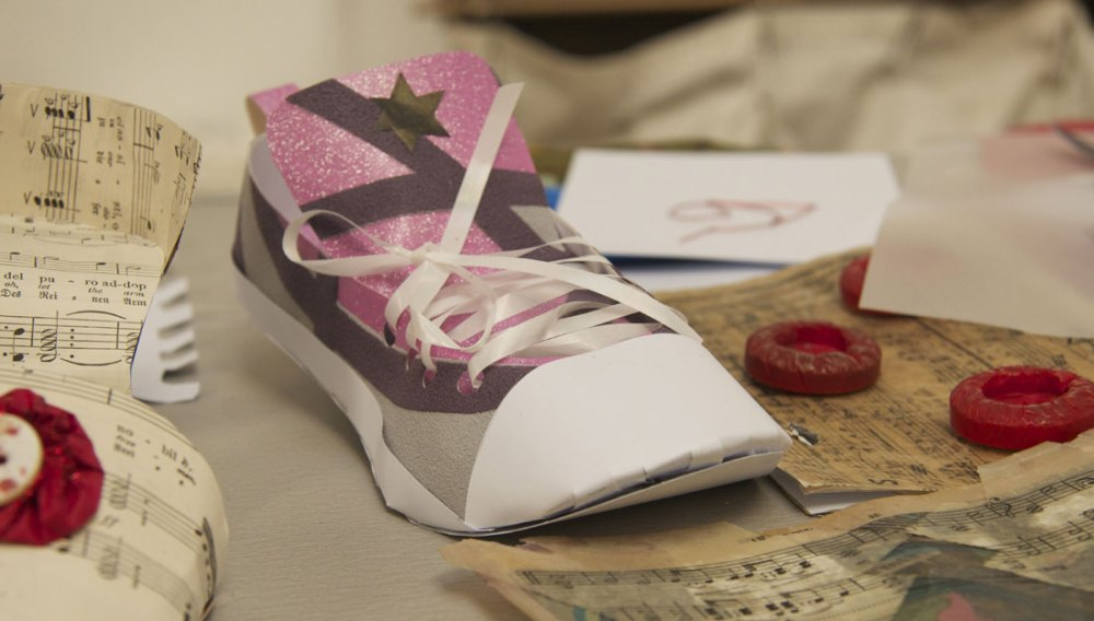 A small shoe made out of paper.
