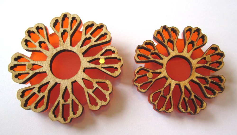 Large and small orange brooches made by Shelanu.
