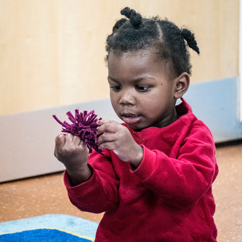 a very young girl looks closely at a pom pom and pulls on the strands of fabric.