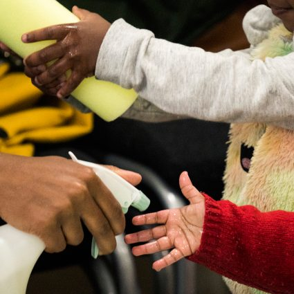 Busy hands. An woman sprays water on a babies hand. A young child feels the texture of material.