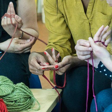hands and t-shirt yarn. Finger knitting.