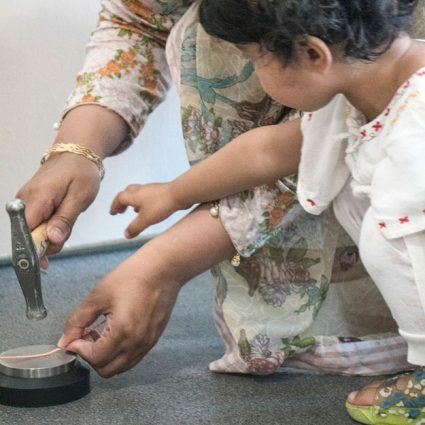 A very young girl reaches for a jewellers hammer being used by an older asian lady.