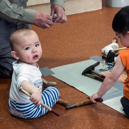 A baby uses a jeweller's hammer.