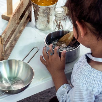 A toddler stirs objects in a saucepan.