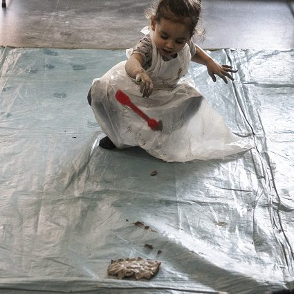 A little girl explores throwing clay and plastic tools onto a plastic sheet.