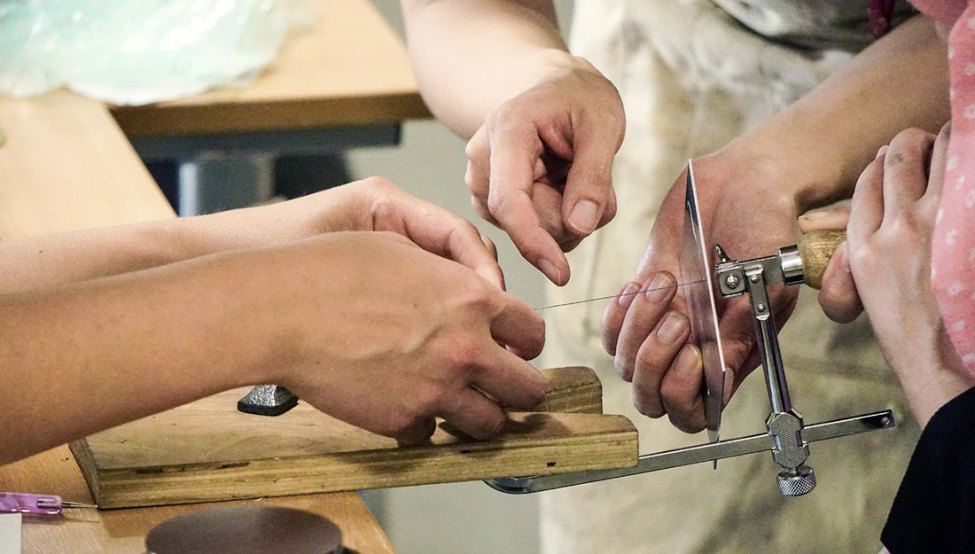 Hands helping an individual place the blade into a piercing saw.