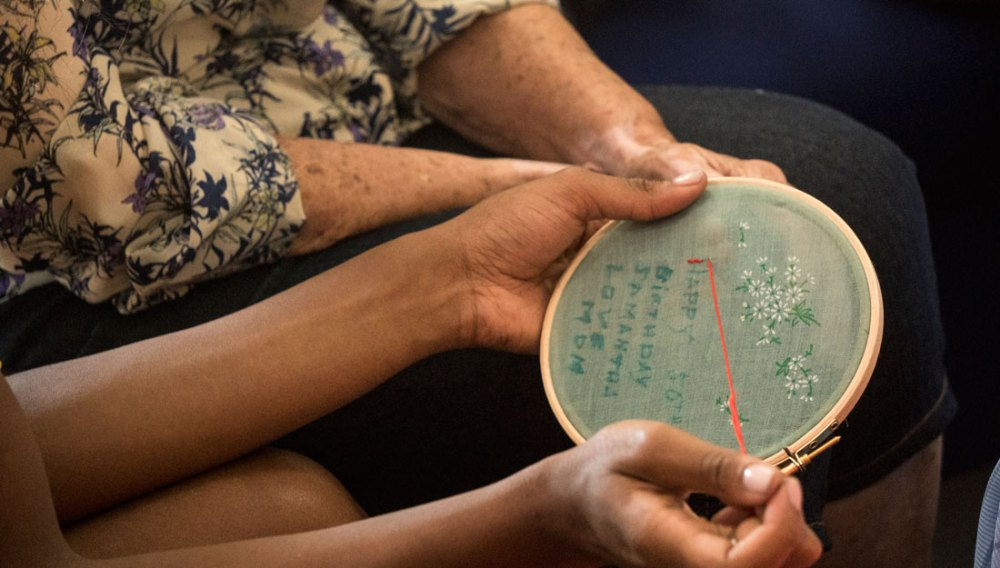 Hands embroidering on to material using an embroidery hoop.