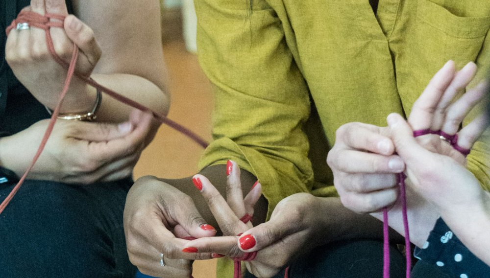 Multiple people use their hands to finger knit with yarn.