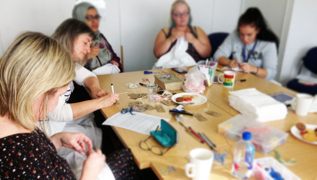 A group of 5 women sit around a table, concentrated. Some are embroidering baby muslins.