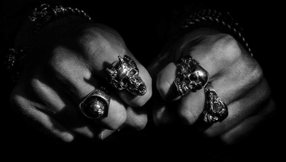 Black and white photo of clenched fists with four silver skull rings