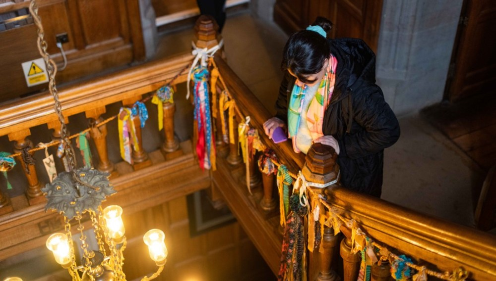 A delegate looks down the stairs at Gawthorpe Hall where there are strips of colourful fabric hanging from bannister