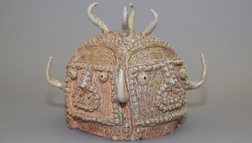 ceramic sculpture with two faces and horns