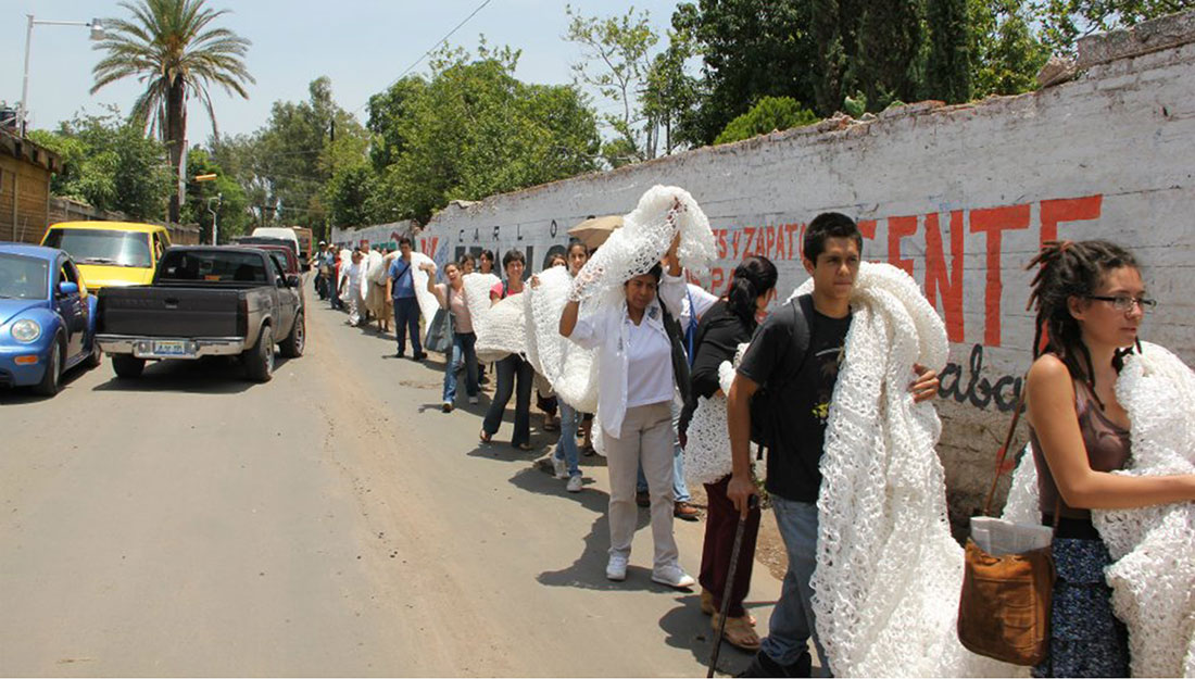 A line of people carry a very large knitted piece on their shoulders.