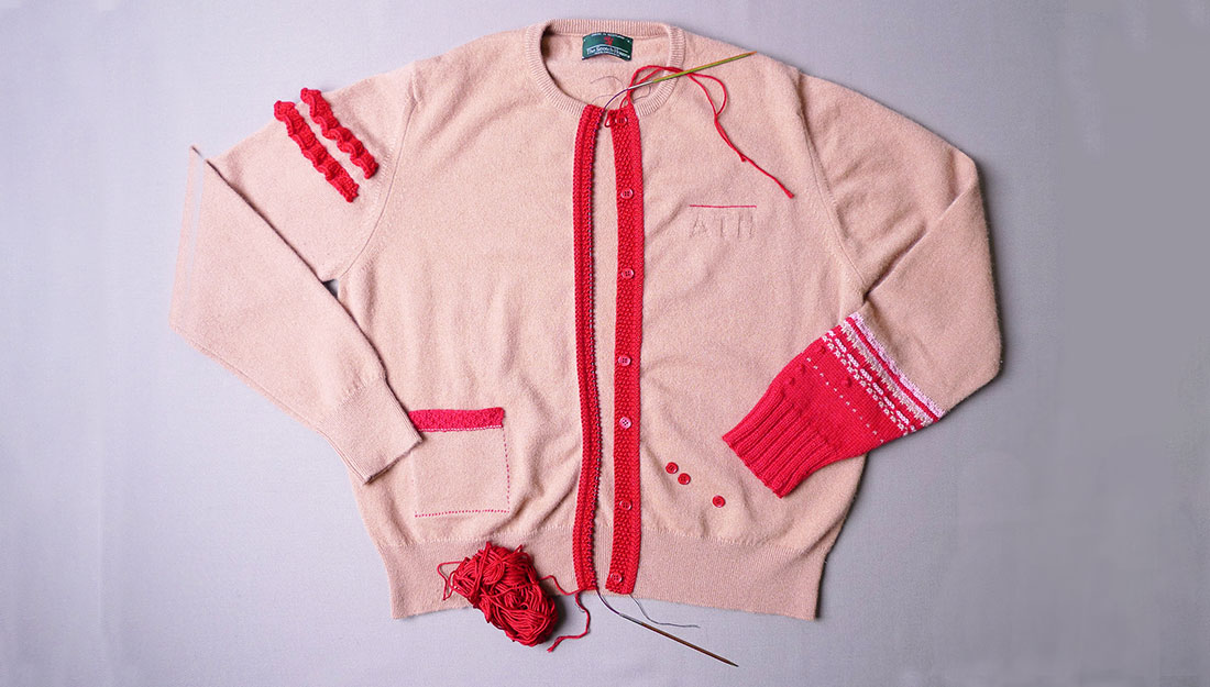 A pink cardigan which has sections that have been re-knitted.
