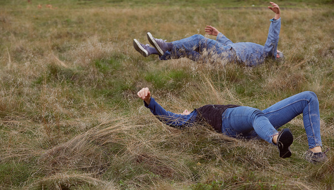 Rehearsing the dance. Two adults roll in the long grass, their legs and arms in the air.