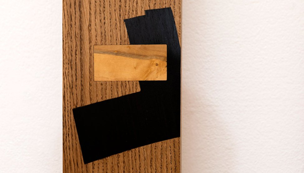 A wooden slat with simple wooden shapes inlaid.