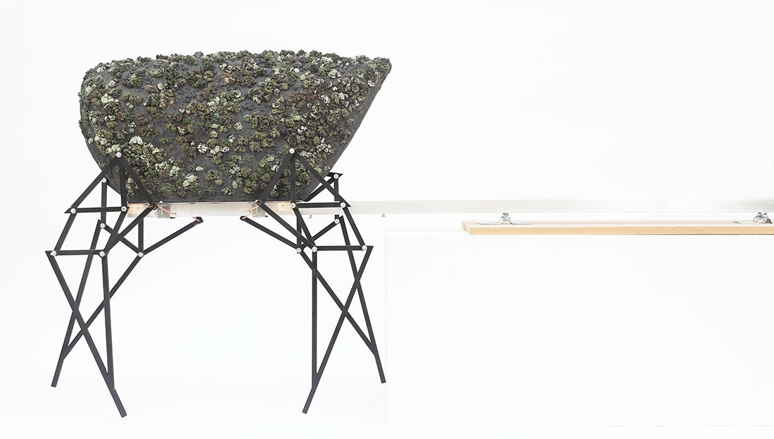 An table-like structure holds a surface covered in ceramic 'moss'.
