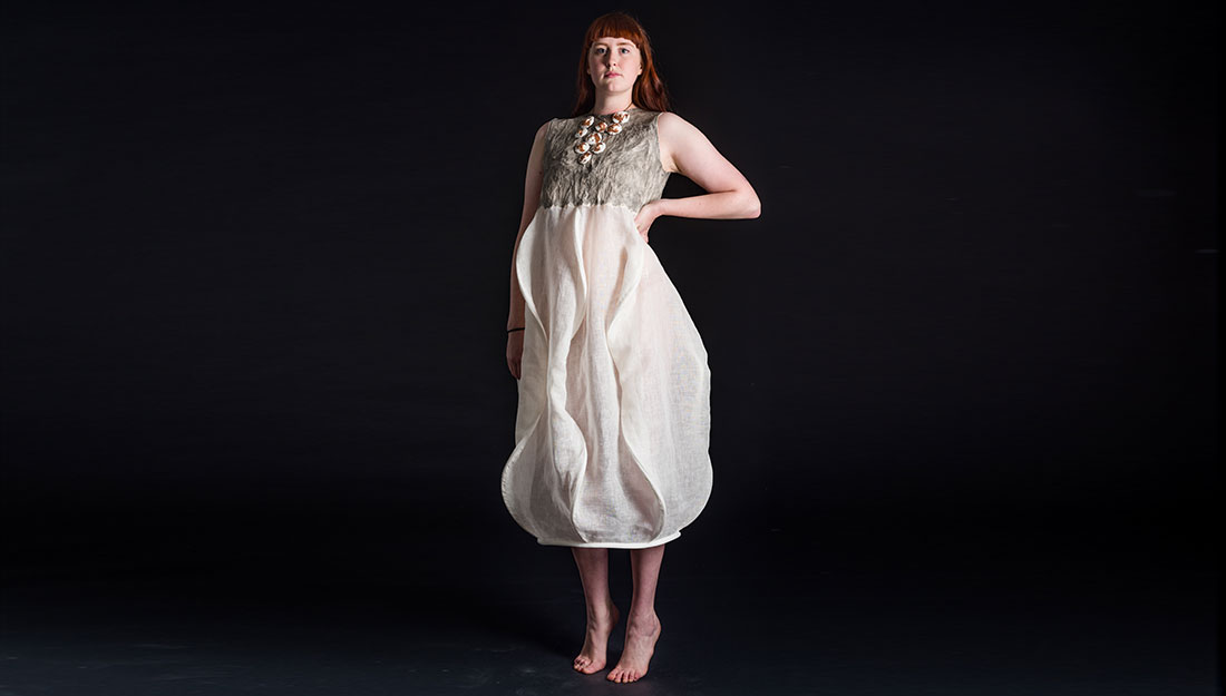 A striking model wears a dress which billows out in the skirt.