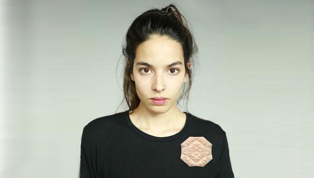 A woman wears a brooch.