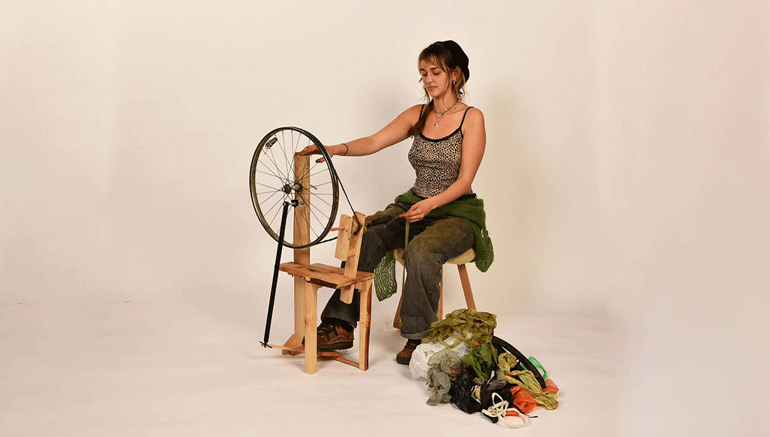 a woman sits at a homemade spinning wheel made from upcycled materials.