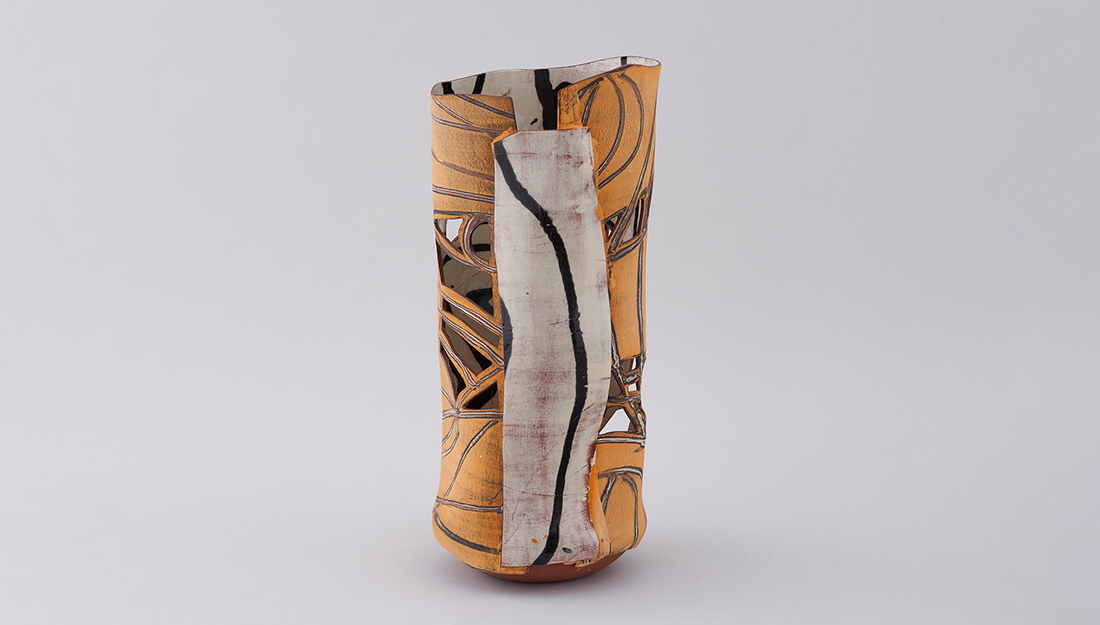 A ceramic vessel with coloured glaze and cut out shapes.