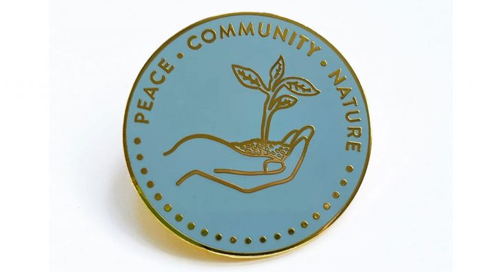 A pale blue enamel badge shoing a line drawing of a hand holding a seedling.