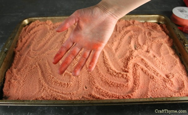 Spreading DIY dyed sand to dry