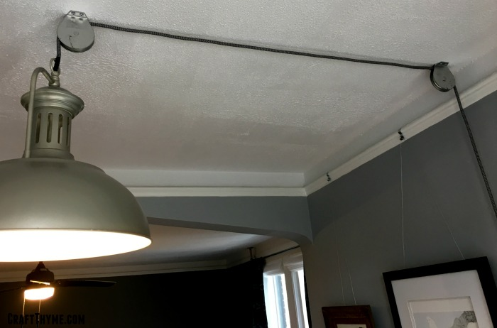 Ceiling mounted pulleys to create an adjustable light.