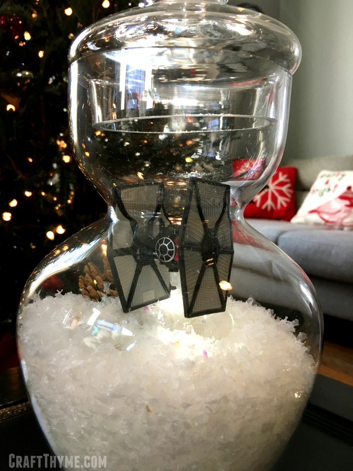 Apothecary jar decorated for Star Wars Christmas with snow and tie fighters.